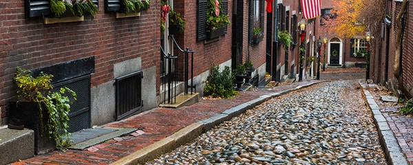 A cobble stone road between two apartment buildings on a Fall day.