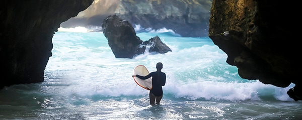 Rear view of surfer carrying a surfboard into the waves of Bali, Indonesia.