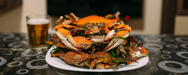 A pile of cooked Maryland blue crabs served with beer.