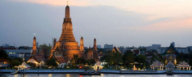 A temple in Bangkok on the Chao Phraya River at night.