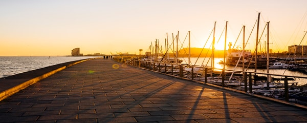 Take a walk along the harbour in Barcelona, Spain at sunset