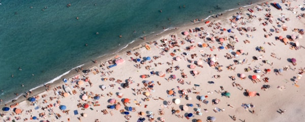 A beach filled with people off the coast of the south of France.