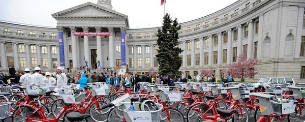 Several people and bikes outside of a county building in Denver.