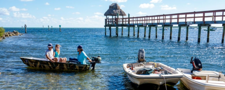 A boat with passengers floats near a pier on the water in Key Largo.