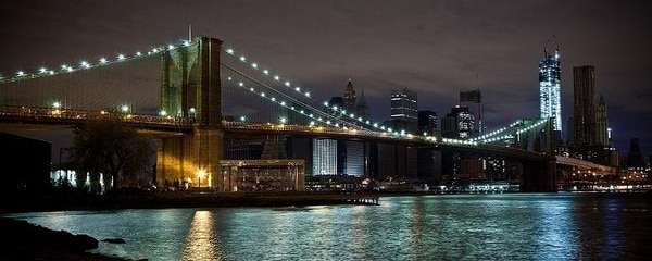 A view of the Brooklyn Bridge illuminated at night.