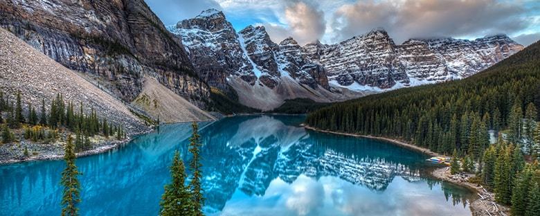 Calgary's calm and serene Moraine Lake surrounded by snow-capped mountains.