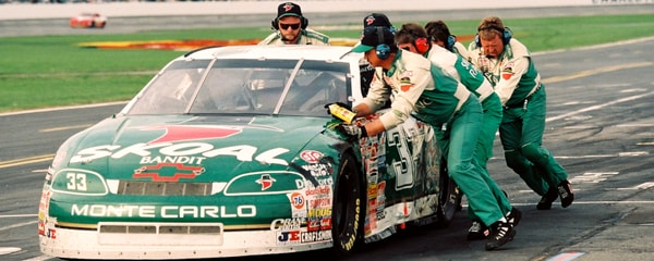 Pit crews work rapidly during a NASCAR race at Charlotte Motor Speedway