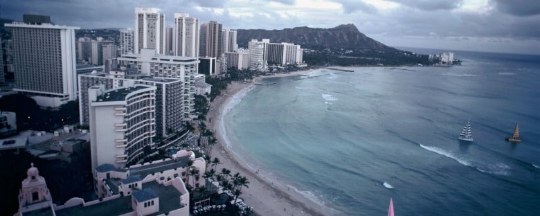 The coast of Honolulu surrounded by the city skyline.
