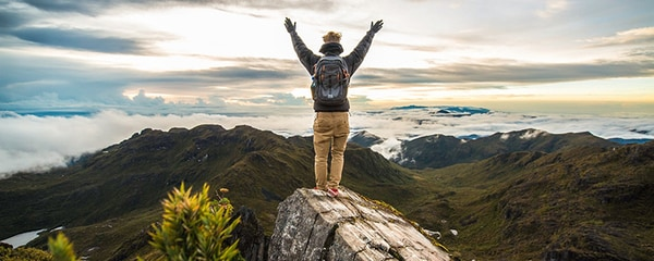Man with his arms raised on a rock at Cerro Chirripo, Costa Rica, with mountains beyond him.