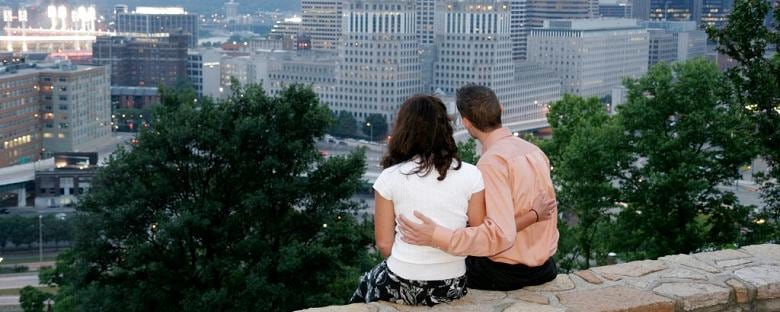 A couple holds each other as they look out on the Cincinnati skyline.