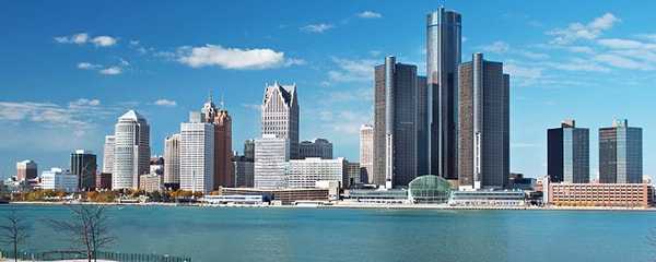 Full view of the Detroit skyline from across the river on a sunny day.