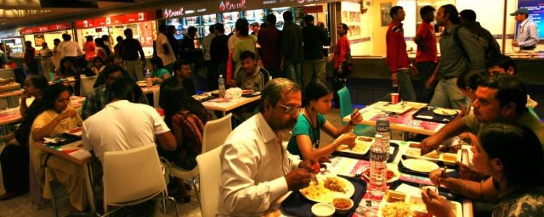 Several diners eating dinner at a Bangalore food court.