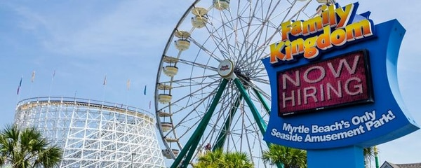 Angled view of a Ferris wheel and Family Kingdom sign under a blue sky in Myrtle Beach.