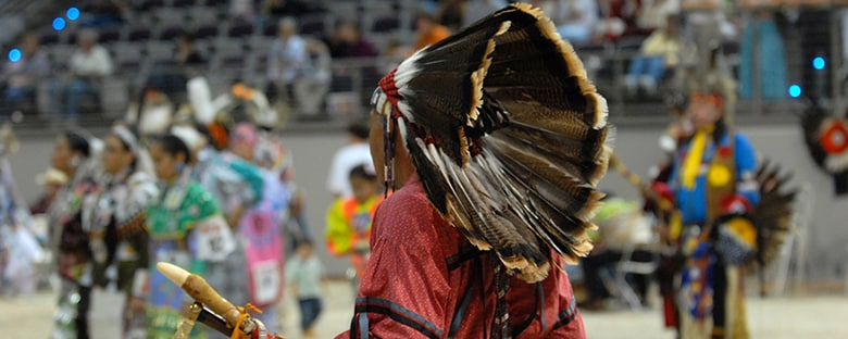 American Indian chief in a traditional dress with others in the background.