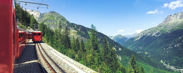Eye level view from train tracks looking over the French Alps on a summer day.