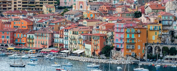 Birds eye view of house boats floating along the French Riviera with colorful building behind them.