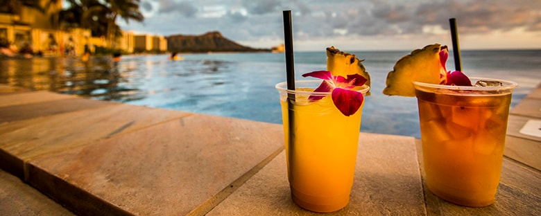 Close up view of fruity cocktails on a beach at sunset in Hawaii.