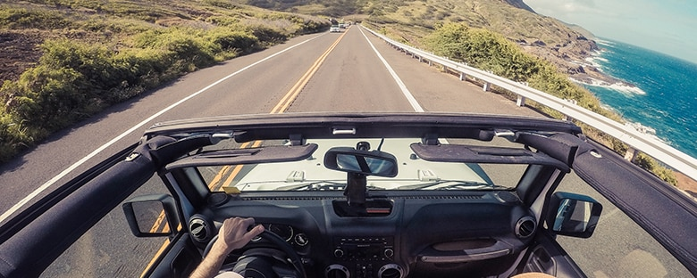 View of the coastal highway in Hawaii from the top of a convertible.