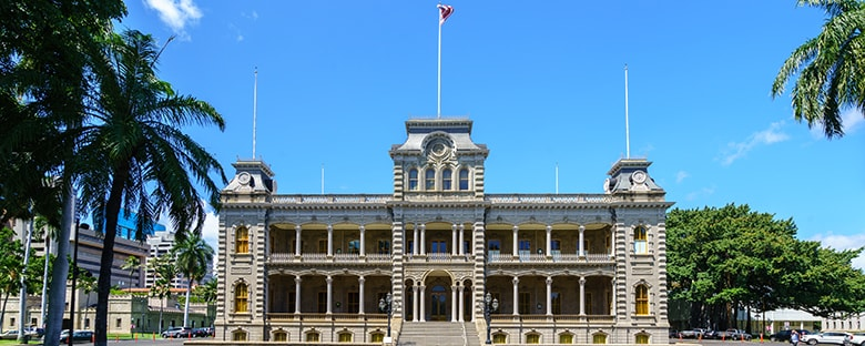 Full view of Iolani Palace in Hawaii on a sunny day surrounded by green trees.