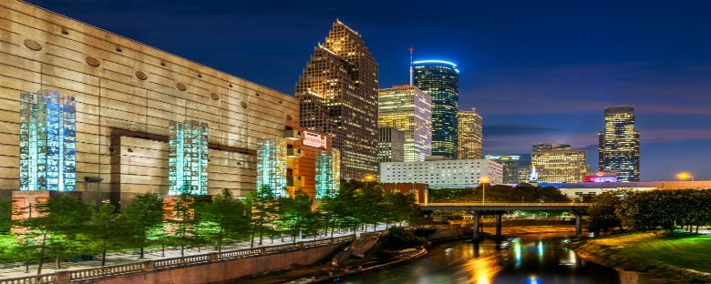 The Houston cityscape illuminated at night along a river.