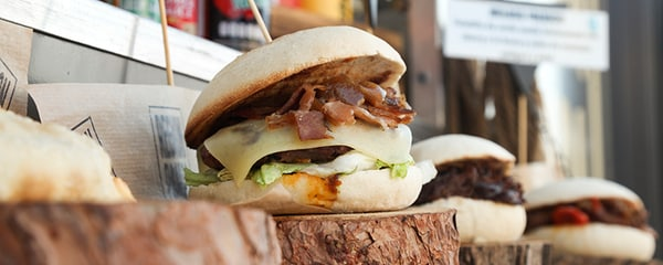 Close up view of a burger sitting on a wooden pedestal.