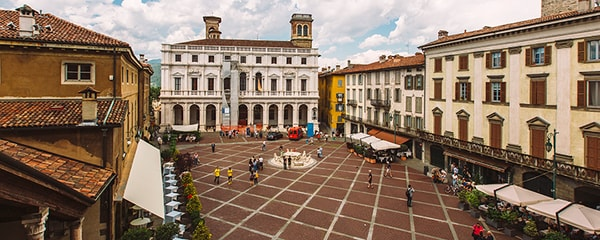 High angle view in Piazza Vecchia surrounded by buildings and people in Lombardy, Italy.