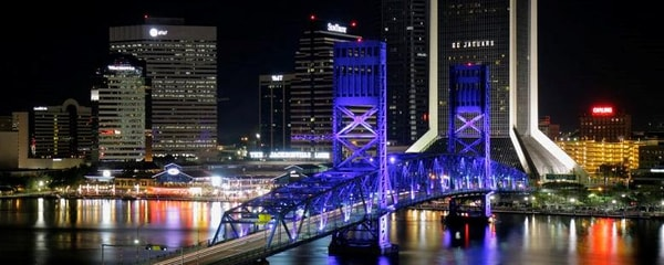 The Jacksonville skyline behind a bridge glowing at night.