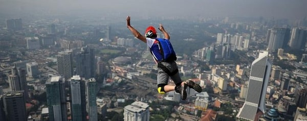 Side view of a jumper in mid air leaping off of Kuala Lumpur Tower.