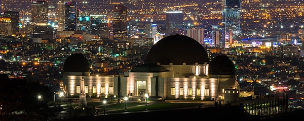 Full view of the Griffith Observatory at nighttime with downtown Los Angeles in the background.