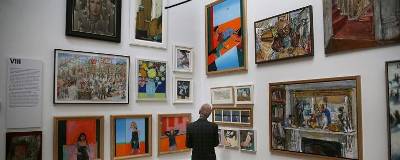 A man is viewing different pieces of art at a gallery in Mayfair, London.