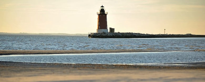Full view of a light house sitting at Cape Henlopen on Delaware Bay in the evening sunlight.