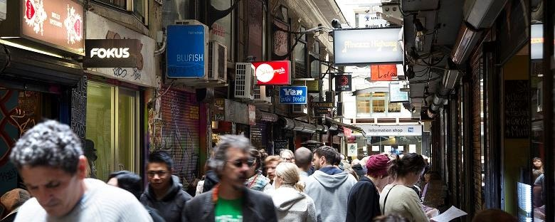 Eye level view of shoppers walking through boutiques in the city center of Melbourne.