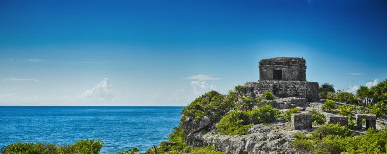 Full view of ancient ruins sitting on top of a hill overlooking the ocean in Tulum, Mexico.
