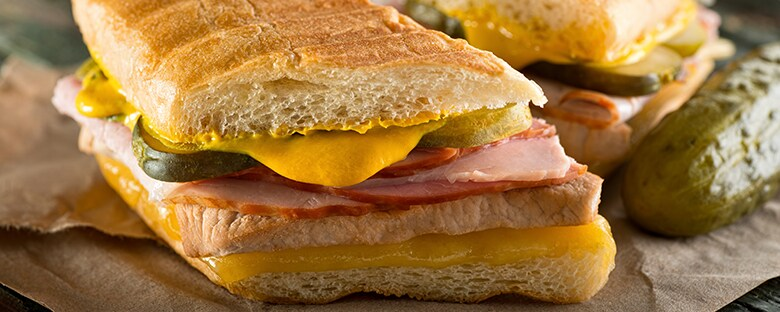 Close up view of a Cuban Cubano sandwich with mustard oozing out.