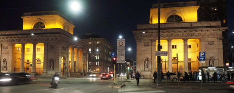 Street view of the Milan Sheraton Diana Majestic at night with people walking in the distance.