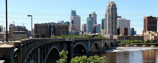 Eye level view from the Third Avenue Bridge in Minneapolis with the city skyline in the background.