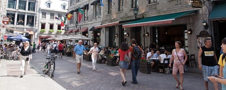 Tourists walking around Montreal on a street full of shops.