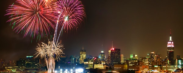 Fireworks display in front of New York City skyline at night.