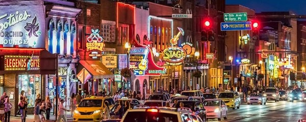 Broadway street lit up at night in Nashville, Tennessee.
