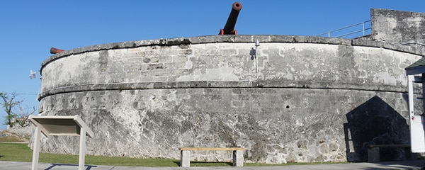 Full view of Fort Fincastle stone wall with an old cannon at the point in Nassau.