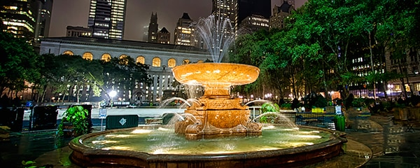 A fountain in Bryant Park flowing in front of New York City's skyscrapers.