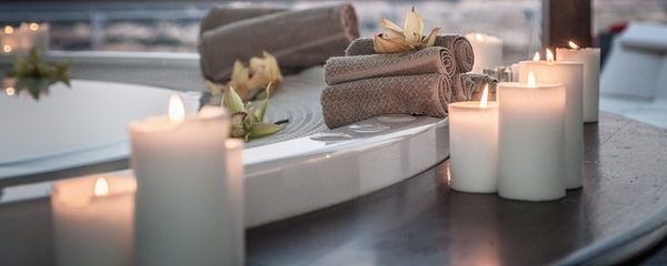 Candles lit in Ottawa spa next to tub lined with towels and flowers.