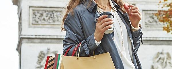 Up-close view of a woman walking with shopping bags, a coffee and a pink macaroon in Paris.