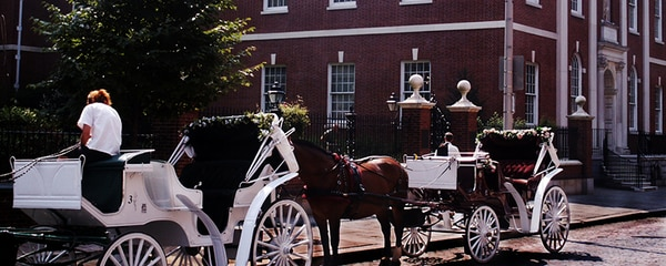 Full view of two horse drawn carriages in Old Philadelphia with a brick building in the background.