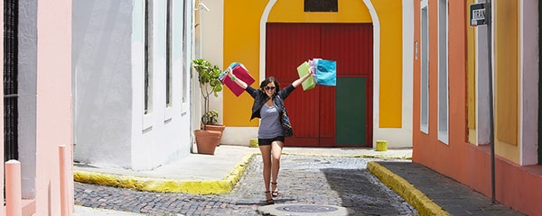 A woman shopping in Old San Juan, Puerto Rico with several bags.