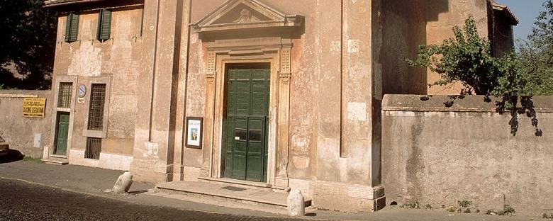Street view of the distressed ancient church of Quo Vadis with a big green door in Rome.