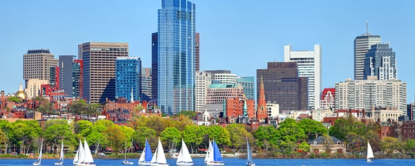 Sailboats along the Boston skyline on a clear day.