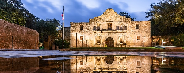 The Alamo reflecting off water in San Antonio, Texas.