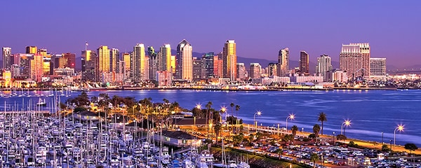 The city of San Diego along the coast at dusk with sail boats floating near by.