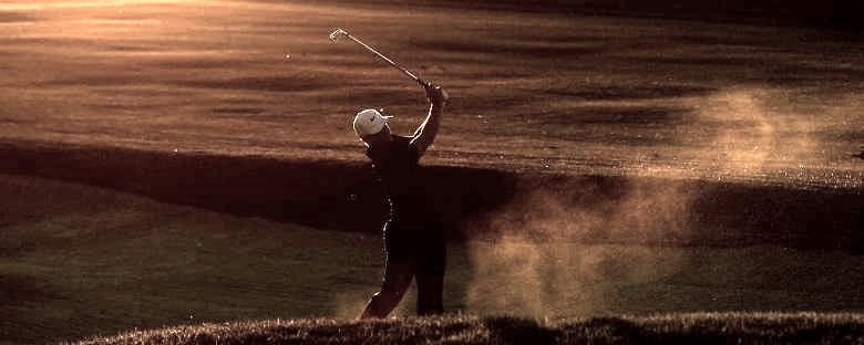 A male golfer takes a swing on a golf course during the sunset in San Diego.